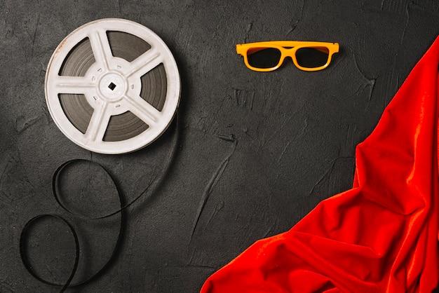 Filmrolle und gläser nahe rotem tuch Kostenlose Fotos