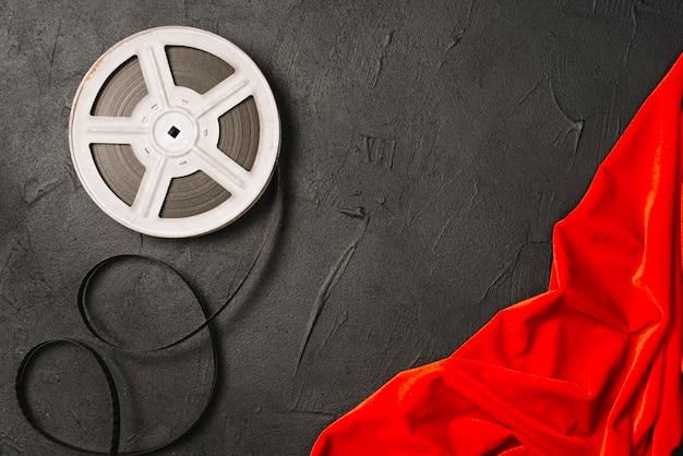 Filmspule nahe rotem tuch Kostenlose Fotos