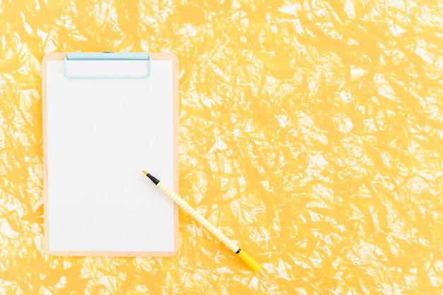 Filzstift auf klemmbrett über dem gelben strukturierten hintergrund Kostenlose Fotos