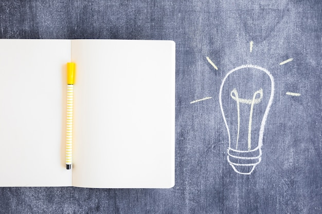 Filzstift auf leerem notizbuch mit gezogener glühlampe auf tafel Kostenlose Fotos