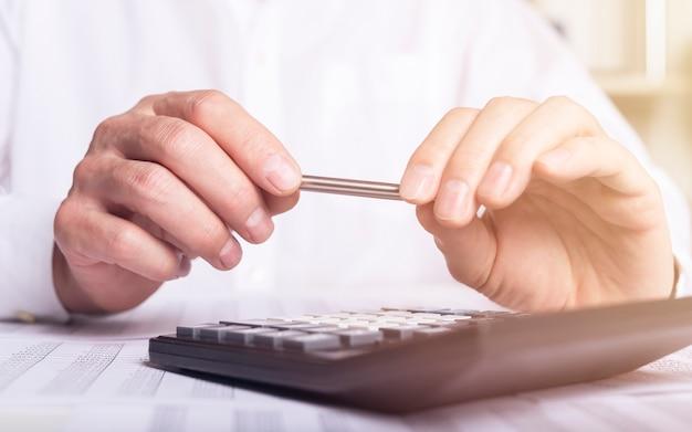 Finanzanalysekonzept, männliche hände, die stift halten und einen rechner über buchhaltungsdokumenten verwenden. Premium Fotos