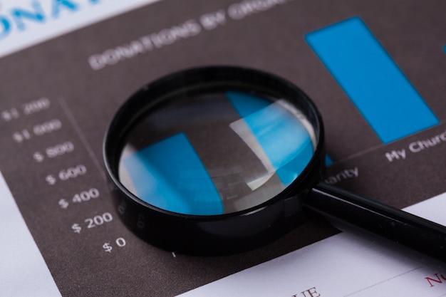 Finanzdokumente mit lupe über ihnen Premium Fotos