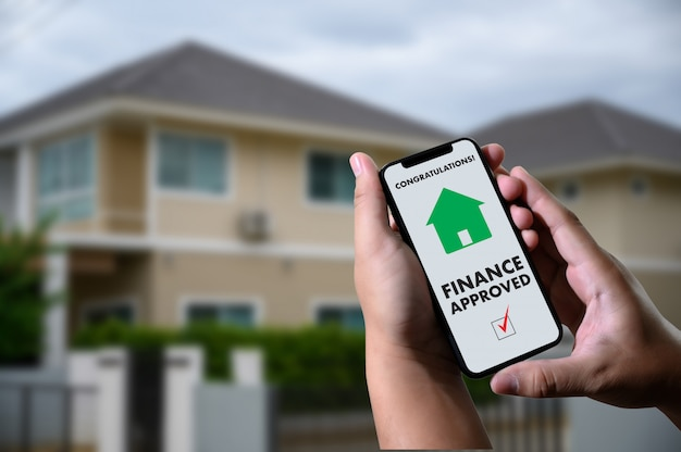 Finanzkreditvertrag und hausschlüssel-hypothekendarlehensgenehmigung am handy in einem haus Premium Fotos