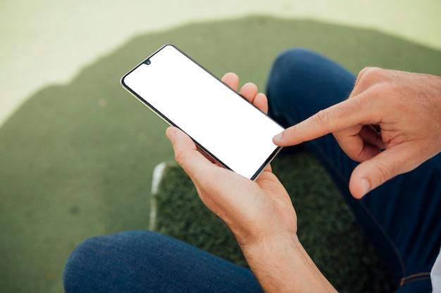 Finger, der auf telefon des leeren bildschirms zeigt Kostenlose Fotos
