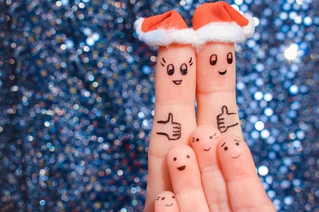 Fingerkunst der großen familie feiert weihnachten. konzept der gruppe von personen lachend in den hüten des neuen jahres. glückliches paar, das sich daumen zeigt. Premium Fotos