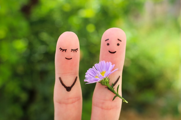 Fingerkunst des glücklichen paars. mann gibt der frau blumen. Premium Fotos