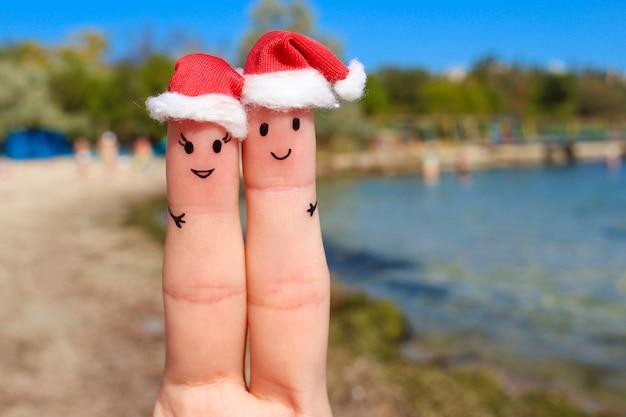 Fingerkunst eines glücklichen paars, das auf dem meer stillsteht. paare, die in den hüten des neuen jahres umarmen. Premium Fotos