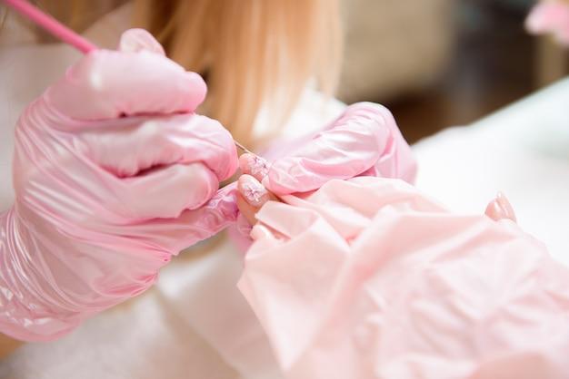 Fingernagelbehandlung, malen mit pinsel und lack. professioneller maniküre-meister in sicherheitsgesichtsmaske. Premium Fotos