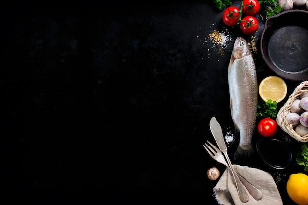 Fisch mit gemüse und besteck auf einem schwarzen hintergrund Kostenlose Fotos