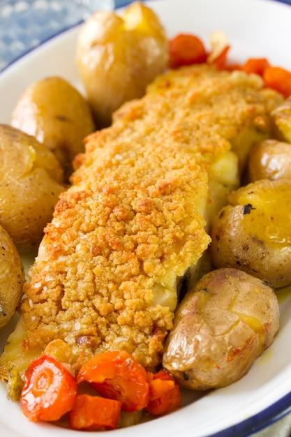 Fisch mit kartoffeln und karotten auf teller Premium Fotos