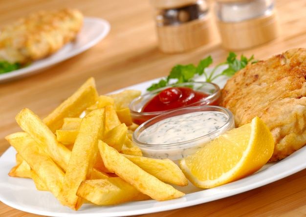 Fisch, pommes, mayo und ketchup auf weißem teller Premium Fotos