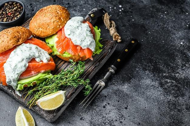 Fischburger mit gesalzenem lachs, avocado, senfsauce, gurke und eisbergsalat Premium Fotos
