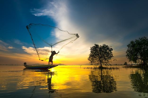 Fischer auf anziehenden fischen des bootes mit sonnenaufgang Premium Fotos