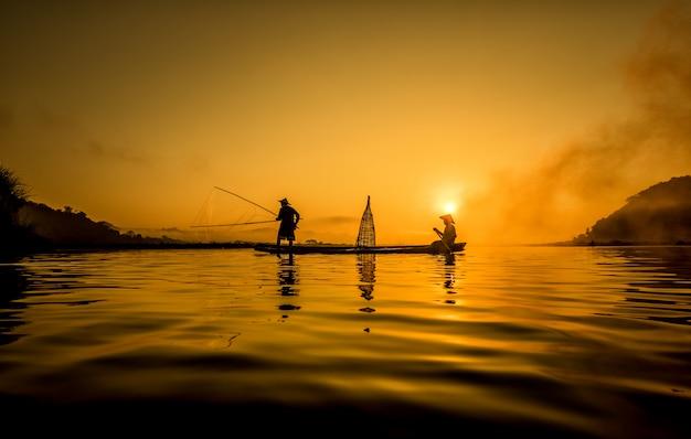 Fischer in aktion beim fischen im see, thailand Premium Fotos