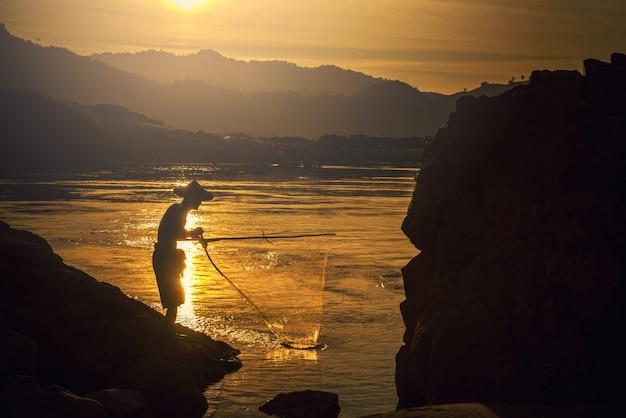 Fischer in aktion beim fischen im see Premium Fotos