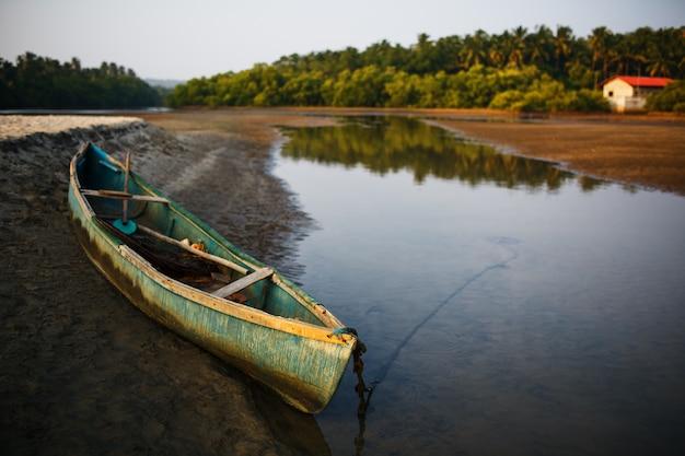 Fischerboot am ufer des flusses in den tropen mit palmen am abend, Premium Fotos