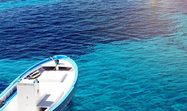 Fischerboot auf einem klaren blauen wasser an einem sonnigen tag. abstrakter hintergrund mit exemplarplatz. Premium Fotos