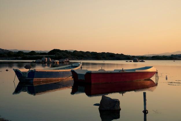 Fischerboot im see bei dem sonnenuntergang Premium Fotos