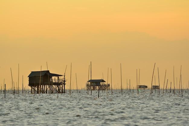 Fischerhaus auf dem meer mit schalentierfarm-sonnenunterganghintergrund in thailand Premium Fotos