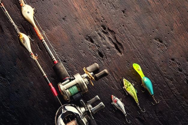 Fischköder, haken und zubehör verdunkeln an hölzernen hintergrund Premium Fotos