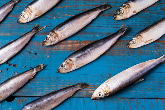Fischmuster. heringfische auf einem alten blauen hölzernen hintergrund. Premium Fotos