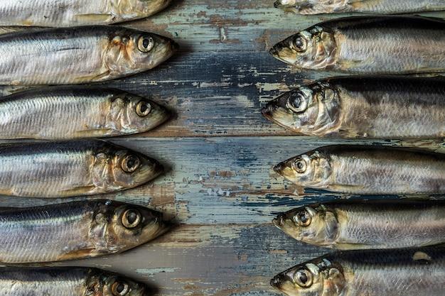 Fischmuster heringsfische auf einem alten blauen hölzernen hintergrund. Premium Fotos