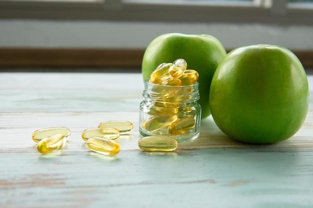 Fischölkapseln und grüner apfel auf holztisch, gesundheitswesenkonzept Premium Fotos