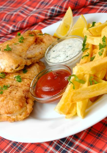 Fish and chips, mayo und ketchup auf roter tischdecke Premium Fotos