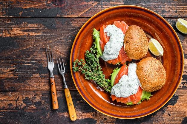 Fishburger mit gesalzenem fischlachs, avocado, burgerbrötchen, senfsauce und eisbergsalat Premium Fotos