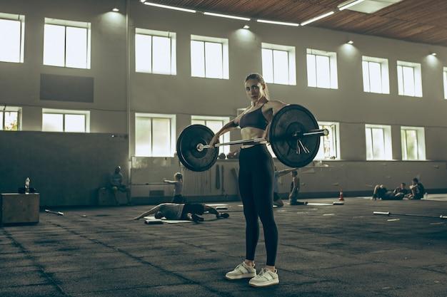 Fit junge frau, die hanteln hebt, die in einem fitnessstudio trainieren Kostenlose Fotos