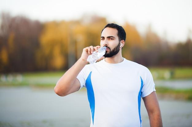 Fitness. erschöpfter läufermann, der auf dem park nach training stillsteht Premium Fotos