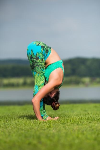 Fitness-frau, die yoga-übung macht und sich mit sportbekleidung im grünen park im sommer entspannt Kostenlose Fotos