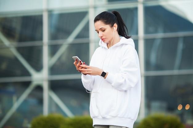 Fitness. hörende musik der frau am telefon beim draußen trainieren - sport und gesundes lebensstilkonzept Premium Fotos