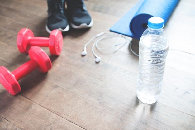 Fitness-konzept mit flasche wasser, sneakers, rote hanteln, yoga-matte und kopfhörer auf holzboden, kopieren sie platz Kostenlose Fotos