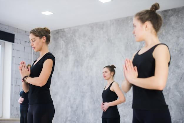 Fitness, meditation und gesundes lifestyle-konzept. gruppe von menschen, die yoga in baumhaltung im studio tun Premium Fotos