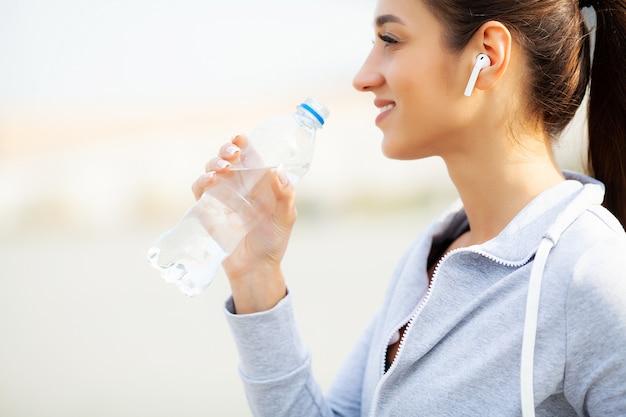 Fitness. trinkwasser der schönheit und hören musik, nachdem sie gelaufen ist Premium Fotos