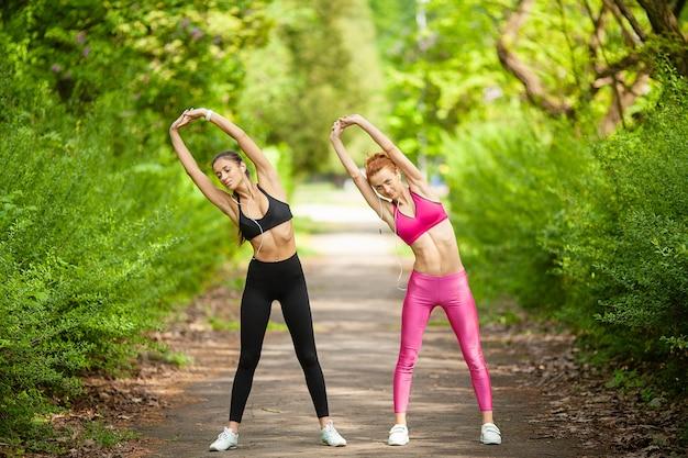 Fitness. zwei weibliche läufer, die draußen beine im park im sommer ausdehnen Premium Fotos