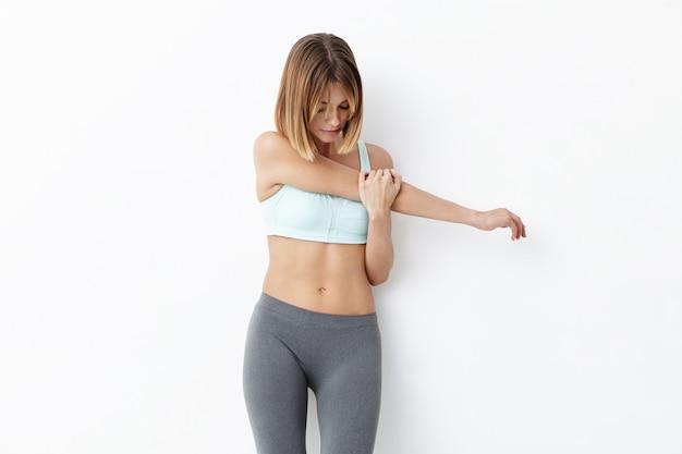 Fitnessfrau mit ansprechendem aussehen, streckt hände Kostenlose Fotos
