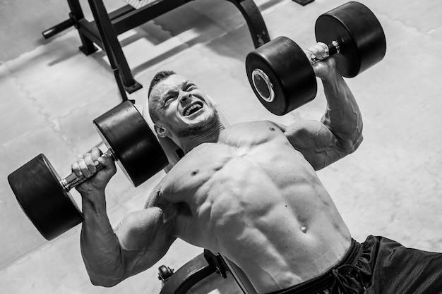 Fitnessstudio. gut aussehender mann während des trainings Kostenlose Fotos