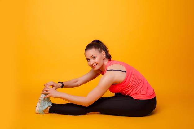 Fitnesstrainer, beinstrecker, gelbe wand Premium Fotos