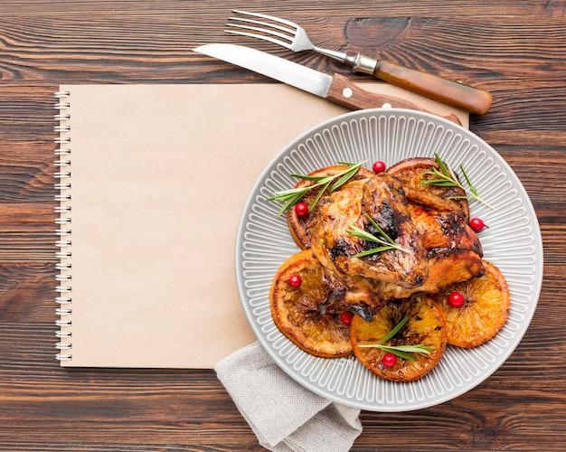 Flach gebackenes hähnchen und orangenscheiben auf teller mit besteck und leerem notizbuch legen Kostenlose Fotos