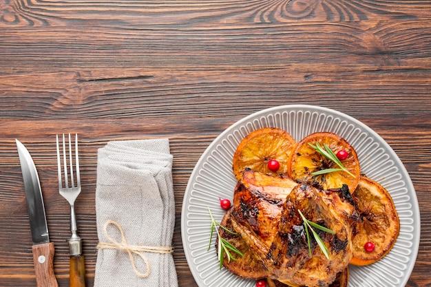 Flach gebackenes hähnchen und orangenscheiben mit besteck und serviette auf teller legen Kostenlose Fotos