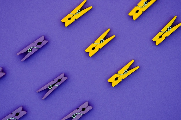 Flach gelegte gelbe und lila wäscheklammern Kostenlose Fotos