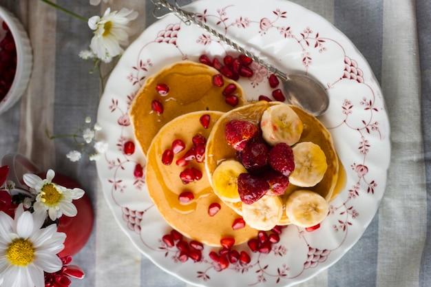 Flach gelegte pfannkuchen mit granatapfelkernen, bananen und himbeeren Kostenlose Fotos