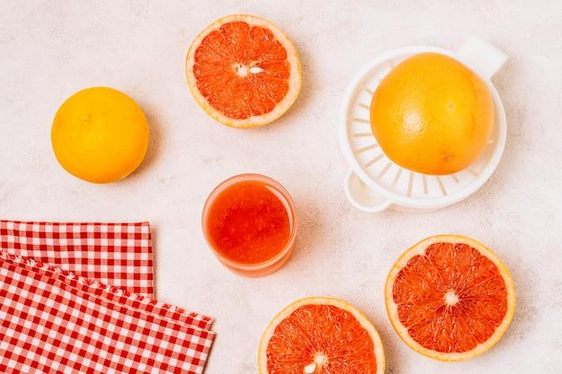 Flach gelegte saftpresse neben halbierten grapefruits Kostenlose Fotos