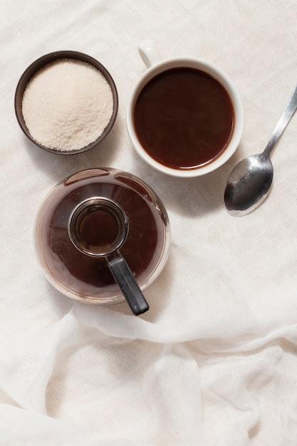 Flach lag schwarzer kaffee in der tasse mit zucker Kostenlose Fotos