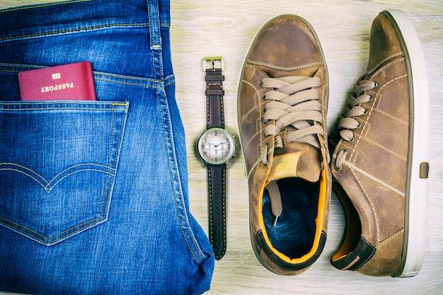 Flach legen blue jeans, schuhe, pass und armbanduhr Premium Fotos