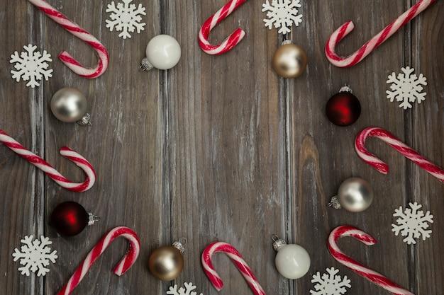 Flach legen kreisförmigen rahmen mit süßigkeiten und schneeflocken Kostenlose Fotos