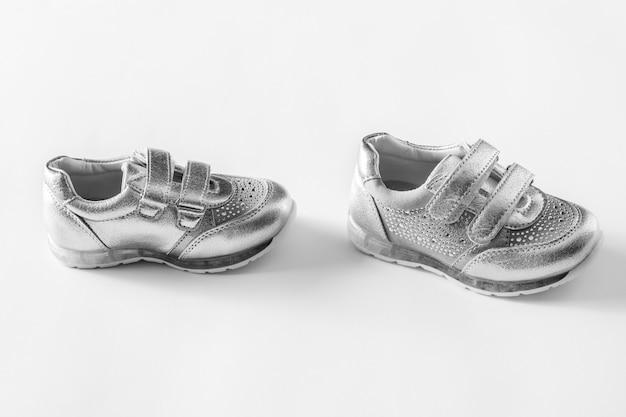 Flach liegen. die silbernen sportschuhe der kinder getrennt auf einem weißen hintergrund Premium Fotos