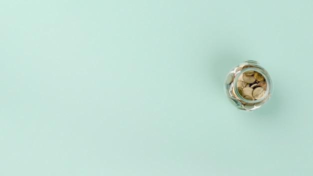 Flach liegendes glas mit münzen Kostenlose Fotos